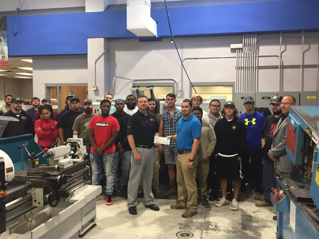 Bill Cranford, Haas Automation, Inc. Sales Engineer presents check to CFCC's Computer Integrated Machining Technology students